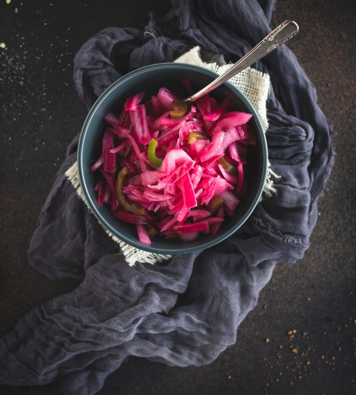 Overhead picture of bowl of pickled red onions on dark background