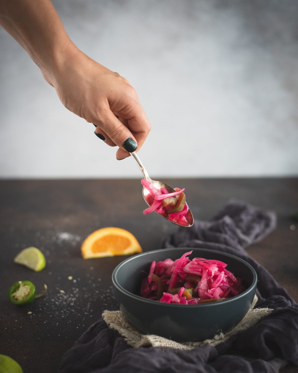 Hand with spoon scooping pickled red onions from bowl
