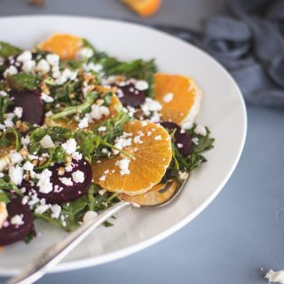 arugula salad on a white plate with beets and orange