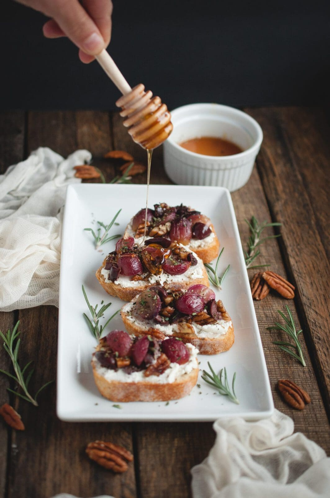 Hand drizzling honey over Crostini with Roasted Grapes, Goat Cheese, and Pecans