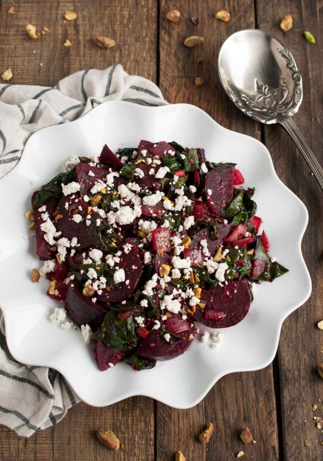 These light, delicious sautéed beet greens are tossed in tangy vinegar and spices before being topped with roasted beets, crushed pistachios, and crumbles of goat cheese.
