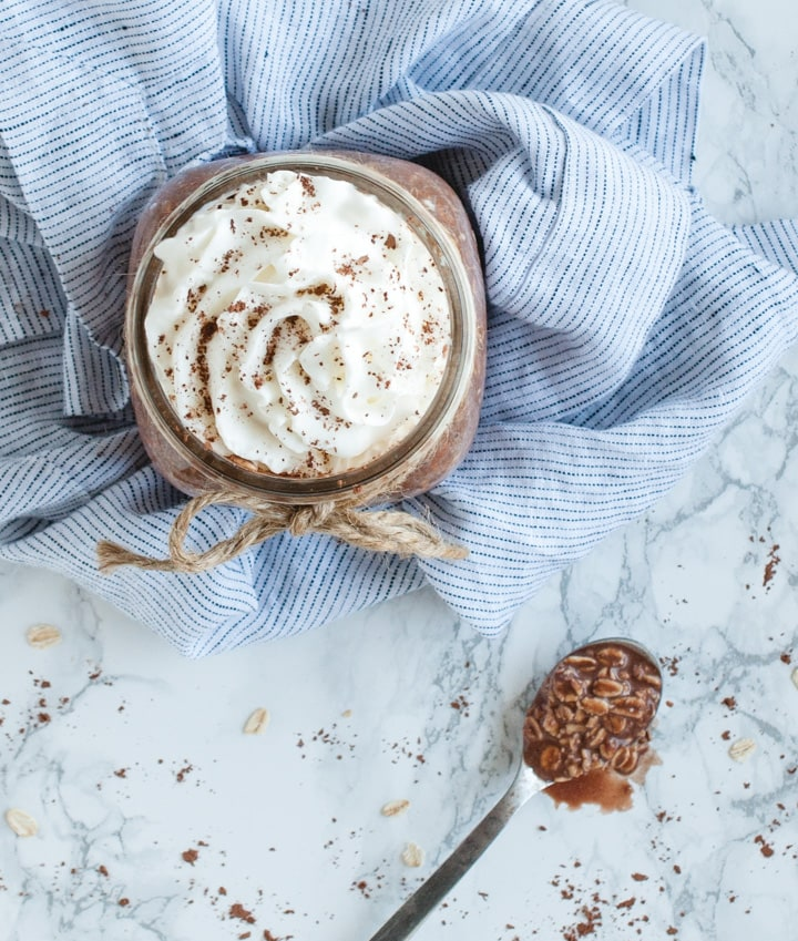 overhead picture of jar with chocolate oatmeal topped with whipped cream and spoonful of chocolate oats next to it