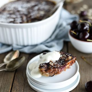 Slice of healthy cherry oat bake with yogurt topping