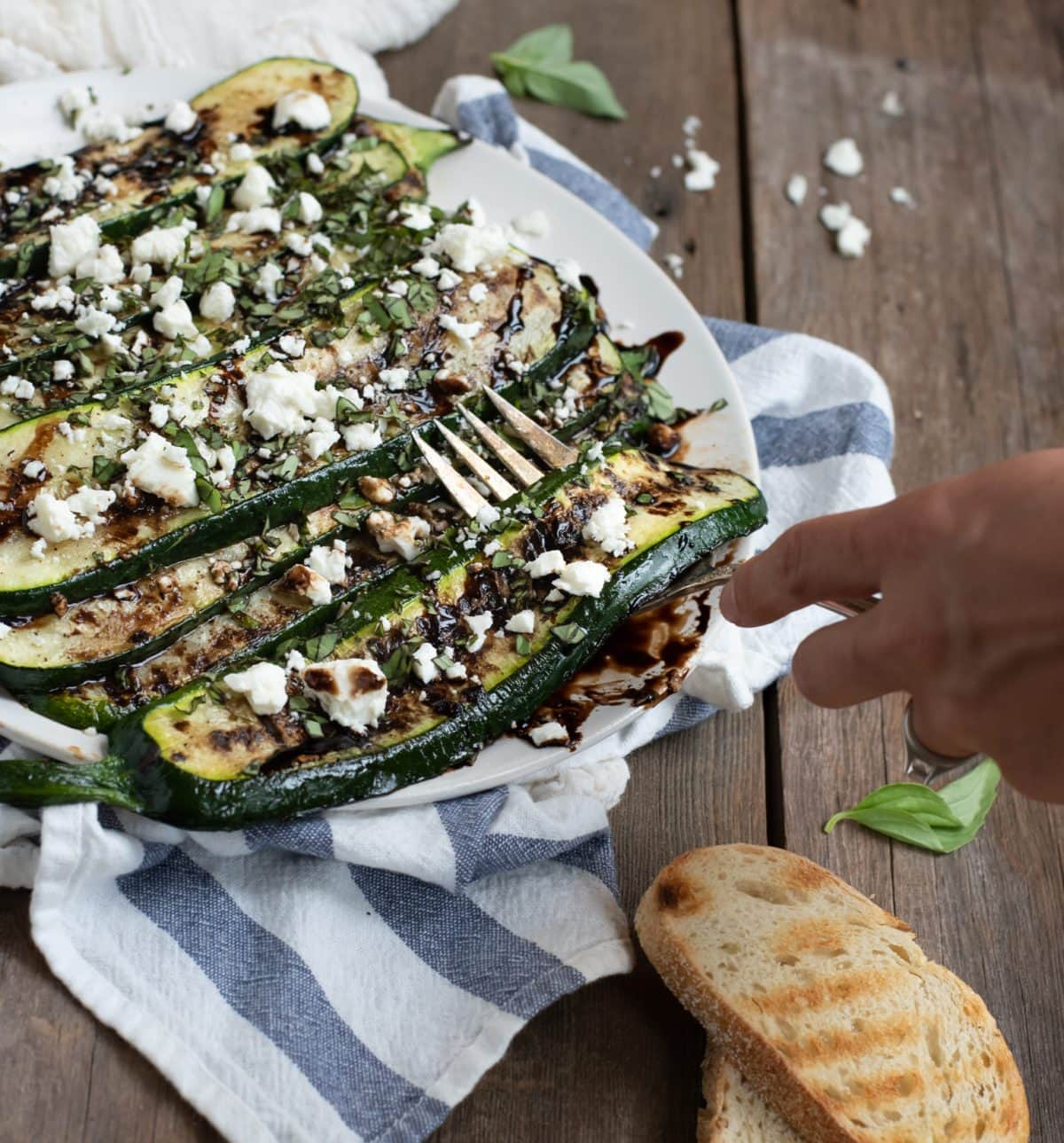 grilled zucchini being lifted with a fork
