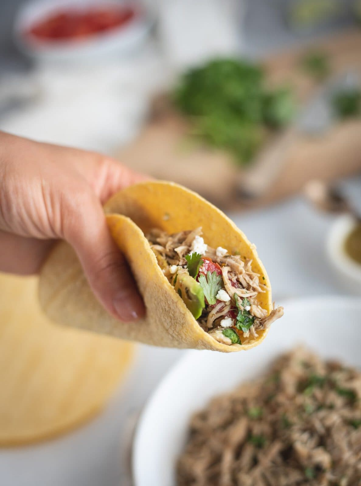 Hand holding Slow Cooker Cilantro Lime Chicken taco