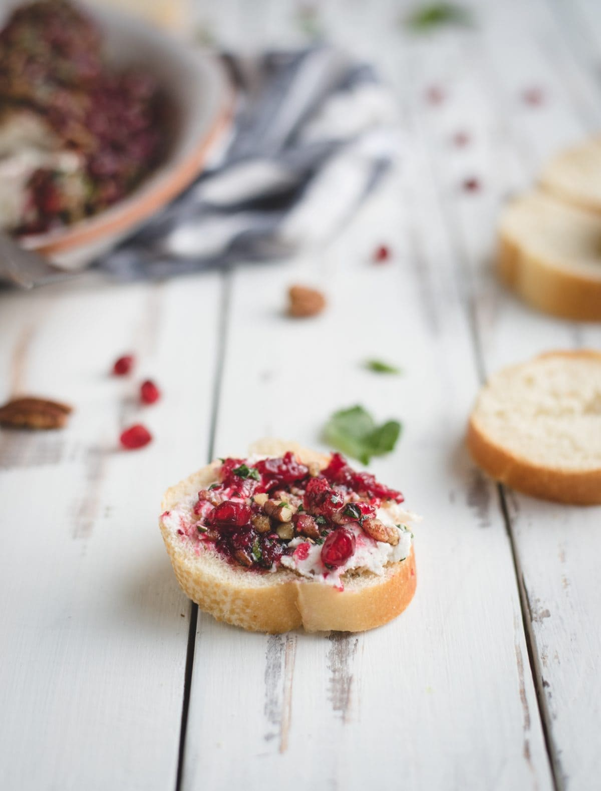 cranberry herb goat cheese log spread on a baguette slice
