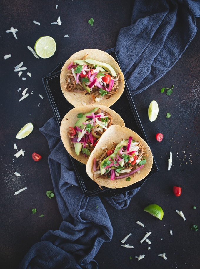 Overhead picture of carnitas tacos on a black background