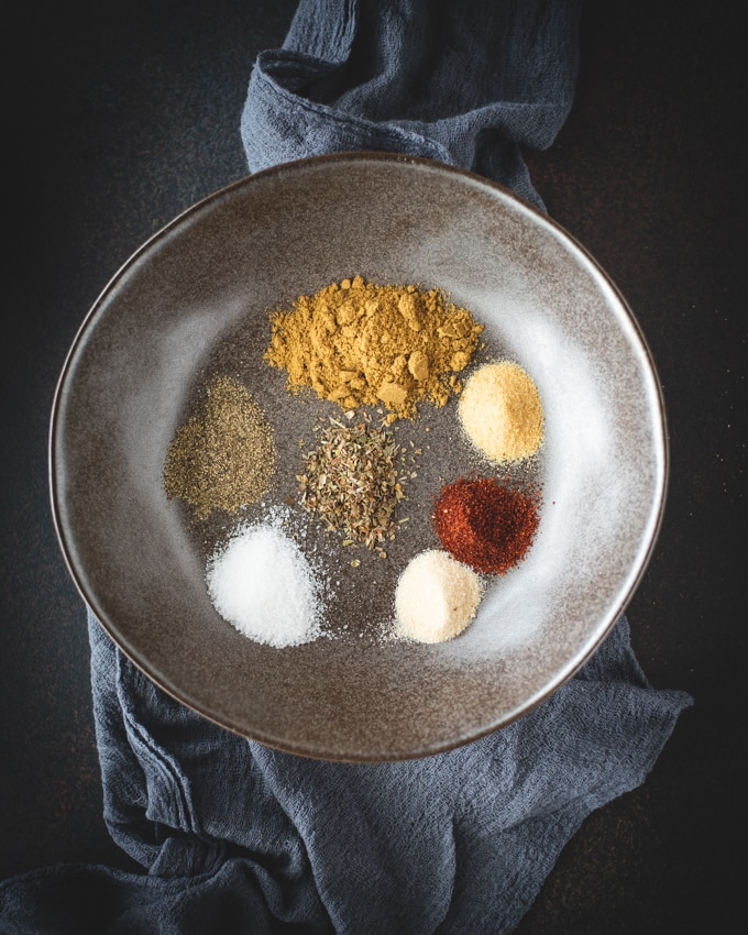 Seven spices on a gray bowl on a black background