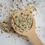 close up picture of wooden spoon with hemp hearts on white background