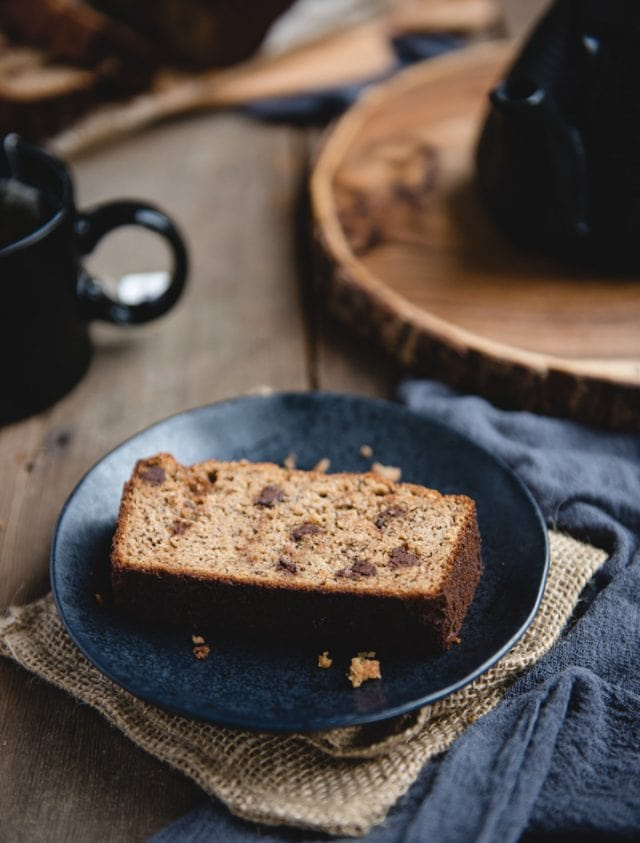 slice of banana bread on a dark plate and wood background
