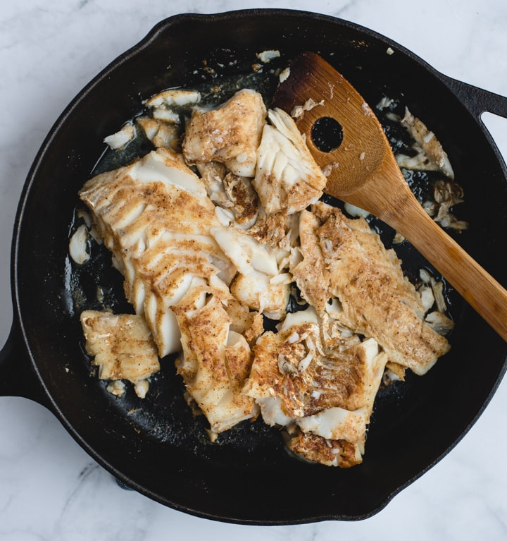 seared fish broken up in a black skillet