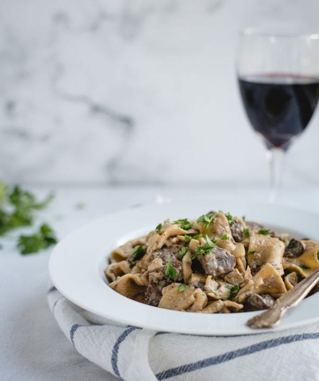 Bowl of beef stroganoff with glass of red wine on white background