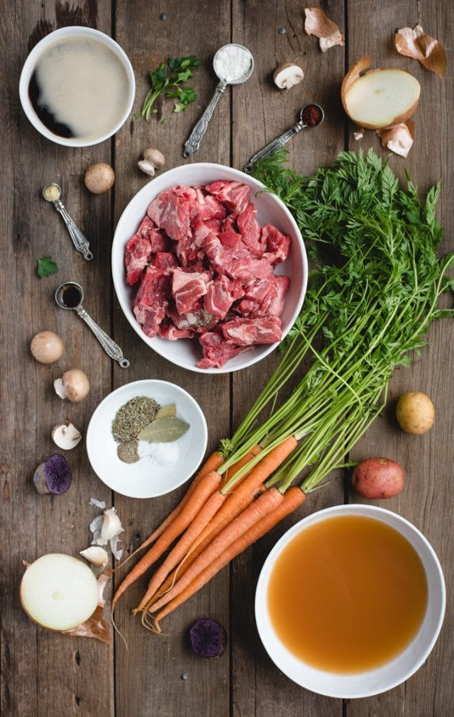 irish beef stew ingredients spread out on a wood background (cubed beef, carrots, broth, spices, etc.)