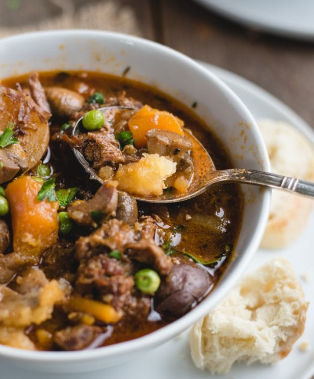 close up picture of spoon resting in bowl of irish stew
